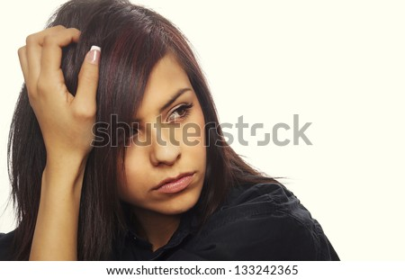 Young woman with serious expression leaning with her hand on hair. - stock photo