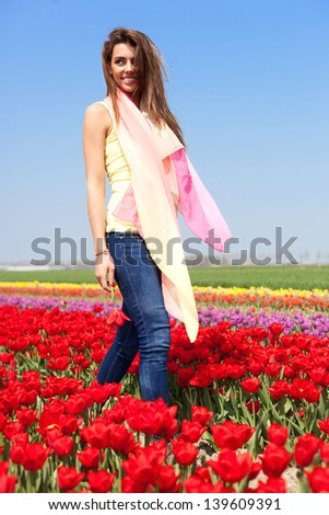 Young woman with shawl enjoying sun and walking  in the red tulip field, outdoors