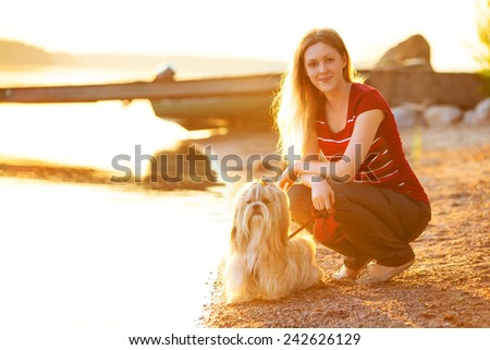 Young woman with shih-tzu dog sitting on lake shore. Red sunset light. - stock photo