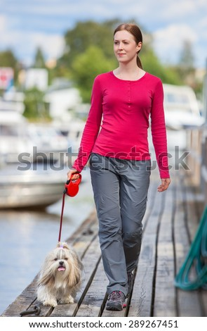 Young woman with shih-tzu dog walking on town quay with boats. - stock photo