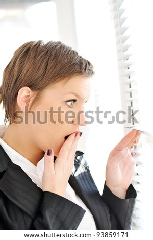 Young woman with shocked expression looking trough window - stock photo