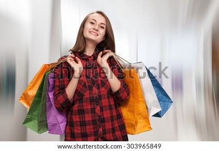 Young woman with shoping bags on blurred background of a trading hall