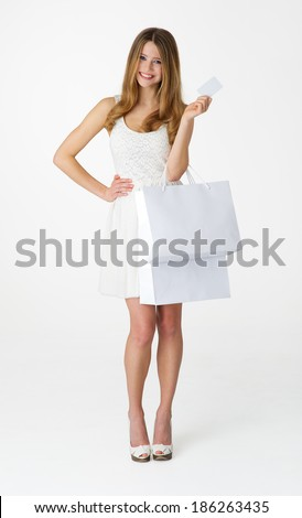 Young woman with shopping bag and card on white background - stock photo