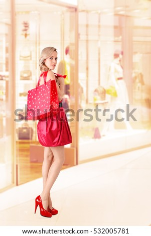 Young woman with shopping bag posing next to store display window