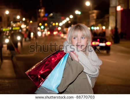 young woman with shopping bags in the city at night - stock photo