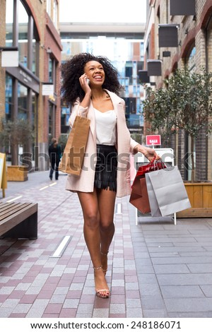 young woman with shopping bags on the phone. - stock photo