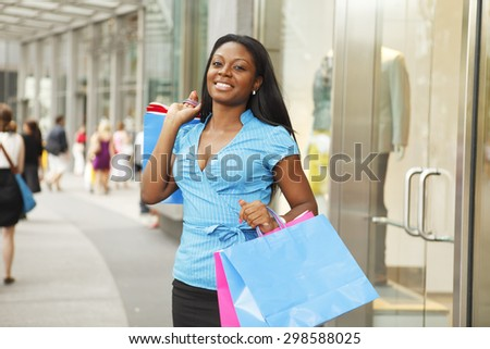 Young woman with shopping bags outside of store. - stock photo
