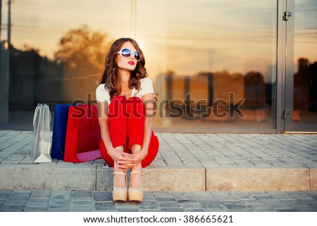 Young woman with shopping bags resting near shop - stock photo