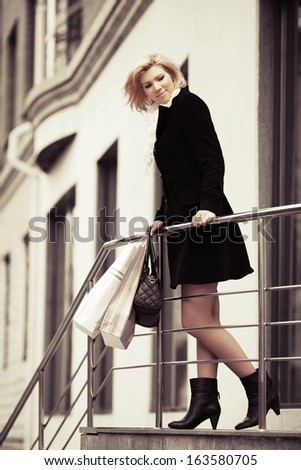 Young woman with shopping bags standing on the mall steps - stock photo