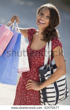 Young woman with shopping bags. Vertically framed shot. - stock photo