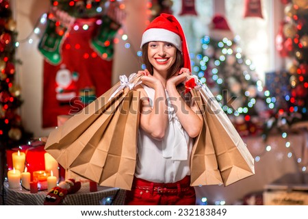 Young woman with shopping bags with Christmas decorations, candles, gifts and lights on bachground. Christmas sale - stock photo