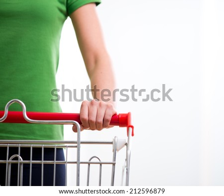 Young woman with shopping cart at supermarket hands close-up. - stock photo