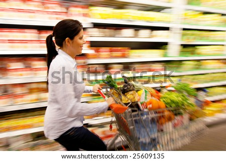 Young woman with shopping cart in the supermarket when shopping - stock photo