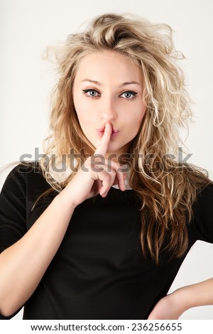 Young woman with silence sign.