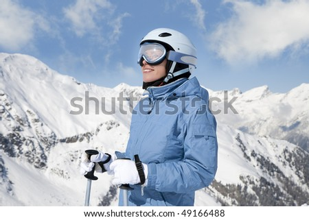 Young woman with ski against mountains - stock photo