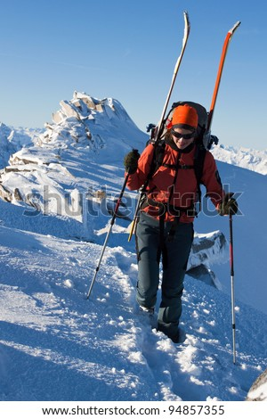 Young woman with ski on a mountain ridge - stock photo