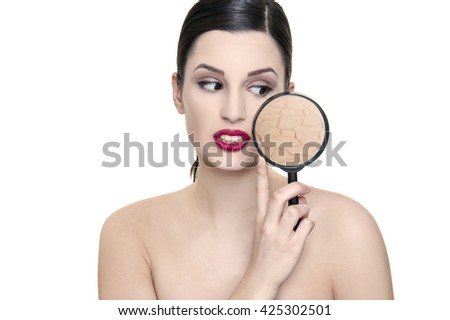 young woman with skin problem under magnifier - stock photo