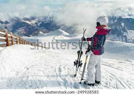 Young woman with skis against a wonderful winter mountains background - stock photo