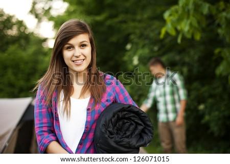 Young woman with sleeping bag - stock photo