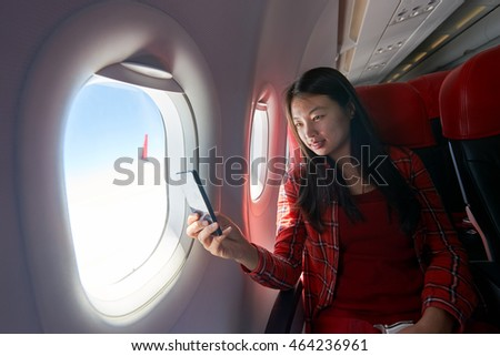Young woman with smartphone inside of a single-aisle aircraft.