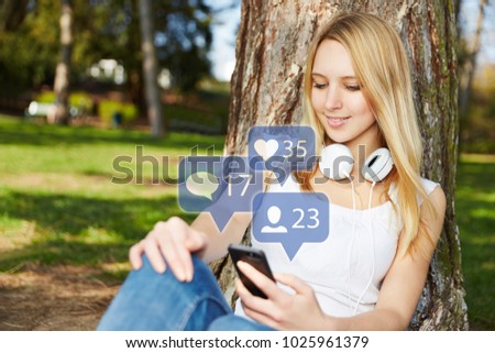 Young woman with smartphone looks at comments on social media