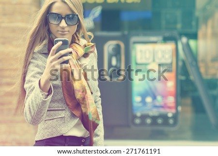 Young Woman with smartphone walking on street, downtown. In background is blured street - stock photo