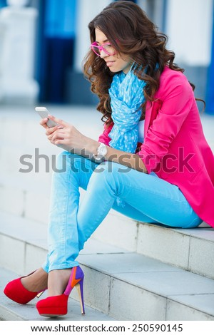 Young Woman with smartphone walking on street, downtown. Young girl sitting on the stairs using cell phone. Emotional smiling portrait.  - stock photo