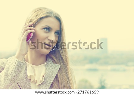 Young Woman with smartphone walking outdoor, downtown. In background is blured city - stock photo