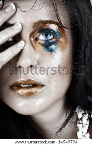 young woman with smudged make-up and face wet from tears with very upset expression - stock photo
