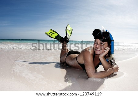 Young woman with snorkel mask and fins laying on the beach with a smile.