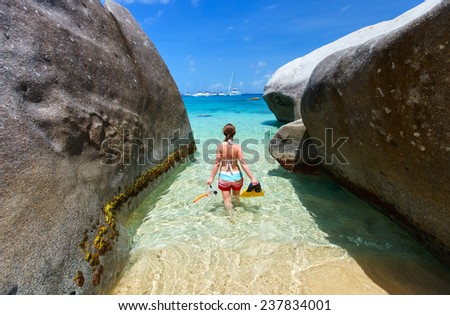 Young woman with snorkeling equipment at tropical beach among granite boulders at Virgin Gorda, British Virgin Islands, Caribbean - stock photo