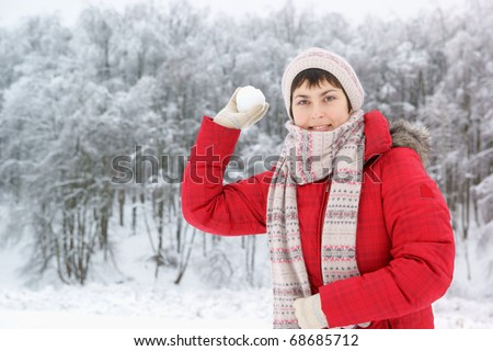 Young woman with snow ball in winter forest - stock photo