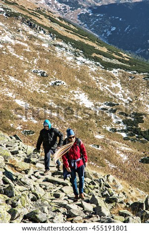 Young woman with son on the mountain footpath leading up the peak Dumbier, Low Tatras, Slovak republic. Hiking theme. Mountains scene. Travelers on the stoned sidewalk. - stock photo