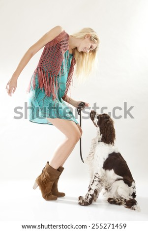 Young woman with spaniel dog wearing Retro Hippie dress - stock photo