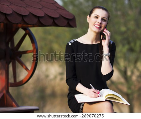 Young woman with speaking on the phone in the park - stock photo