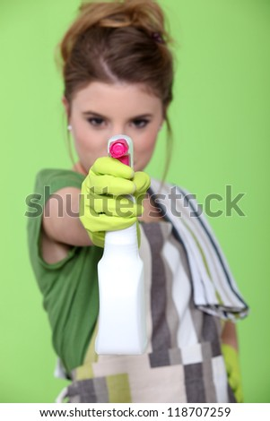 Young woman with spray cleaner - stock photo