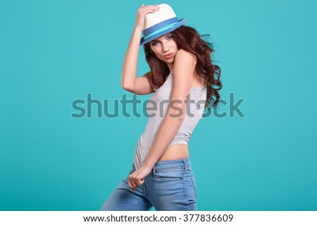 Young Woman with spring hat against blue background  - stock photo