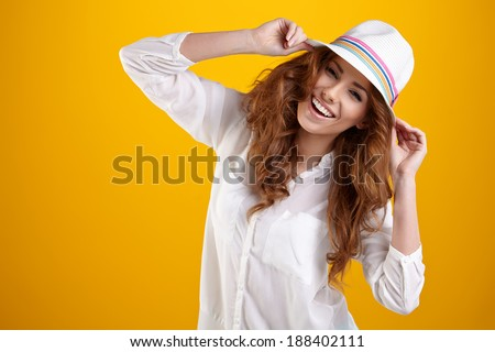 Young Woman with spring hat against yellow background  - stock photo