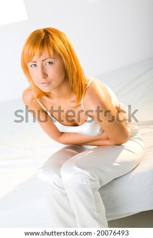 Young woman with stomachache sitting on bed. She's hugging her abdomen. Looking at camera. - stock photo