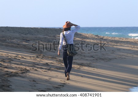 Young woman with straw hat walking on the beach - stock photo