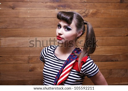 Young woman with striped T-shirt on wooden background