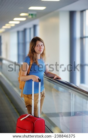 Young woman with suitcase at the airport  - stock photo