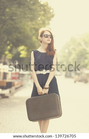 Young woman with suitcase on the city street - stock photo