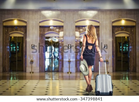 Young Woman with suitcase walking at the hotel lobby - stock photo