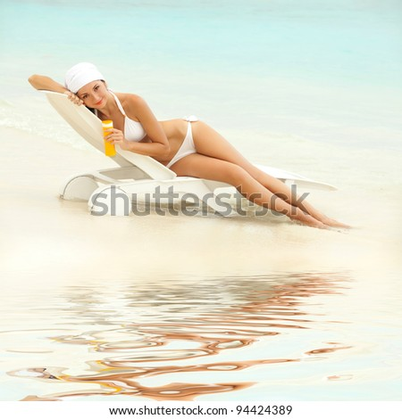 Young woman with sun-protection cream on the beach - stock photo