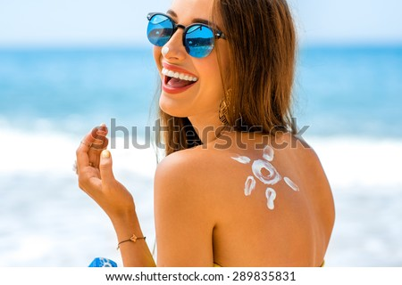 Young woman with sun shape on the shoulder holding sun cream bottle on the beach  - stock photo