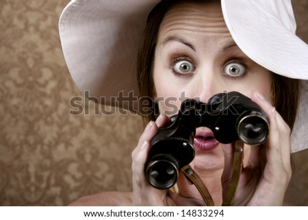 Young Woman with Sunglasses and a Floppy White Hat Looking through Binoculars - stock photo