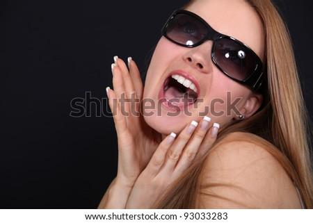 Young woman with sunglasses screaming in front of a black background - stock photo
