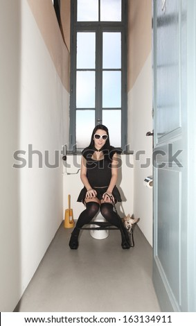 young woman with sunglasses sitting on the toilet, interior