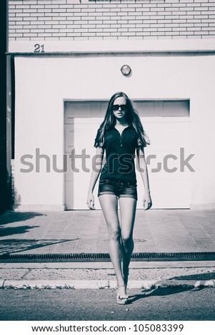young woman with sunglasses walk down the street, summer day, black and white - stock photo